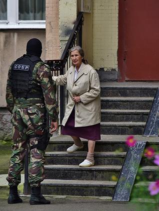 Сотрудники правоохранительных органов во время проведения спецоперации по задержанию предполагаемых террористов в жилом доме на Ленинском проспекте. Сотрудник СОБРа разговаривает с жильцом дома.